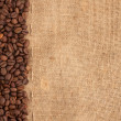 Line of coffee beans and burlap — Stock Photo #13770567
