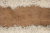 Ris utspridda på säckväv — Stockfoto