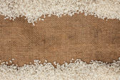 çuval bezi üzerinde dağınık pirinç — Stok fotoğraf