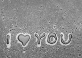 Inscription I love you written on a black background with water — Stock Photo