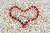 Röda pärlor i form av ett hjärta — Stockfoto