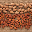 Shelled and unshelled almonds lying on sackcloth — Stock Photo