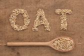 Inscription oat with a wooden spoon on burlap — Stock Photo