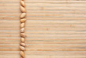 Unrefined pistachios lying on a bamboo mat — Stock Photo
