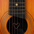 A heart lies on strings the guitar — Stock Photo #24794705