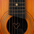 A heart lies on strings the guitar - Stock Photo