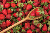Wooden spoon with strawberries — Stock Photo