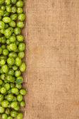 Green gooseberry lying on sackcloth — Stock Photo