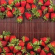Strawberries lying on bamboo mat — Stock Photo