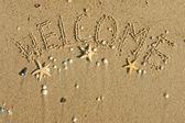 Słowo zapraszamy na piasku — Zdjęcie stockowe