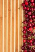 Cherry lying on bamboo mat — Stock Photo