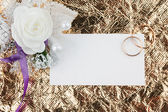 Rings, flowers and invitation on a gold background — ストック写真