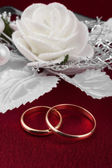 Wedding rings on a red cloth — Stock Photo