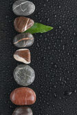 Striped stones and leaf lie on a wet black background — Stock Photo