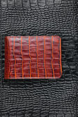 Brown wallet lying on black leather — 图库照片