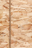 Rope lying on oriented strand board — Stock Photo