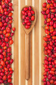 Wooden spoon with rosehip — Stock Photo