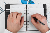 Male hand with pen wrote in a diary — Stock Photo
