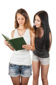 Girl spying on girlfriend  reading a book — Stock Photo