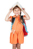 Cute schoolgirl with book on his head and a red backpack on her  — Stock Photo