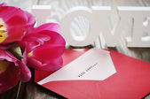 Tulips and red open envelope — Stock Photo