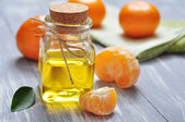 Tangerine oil in a glass bottle — Stock Photo