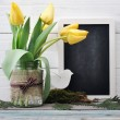 Tulips bouquet with blank blackboard — Stock Photo