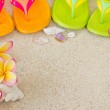Flip Flops in the sand with shells and frangipani flowers. Summe — Stock Photo #12736812