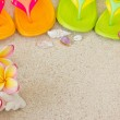Flip Flops in the sand with shells and frangipani flowers. Summe — Stock Photo