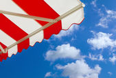 Awning over bright sunny blue sky — Stock Photo
