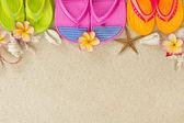 Bunte flip-flops im sand mit muscheln und frangipani flowe — Stockfoto