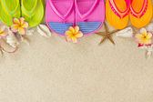Colorful Flip Flops in the sand with shells and frangipani flowe — Stok fotoğraf