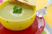Pea cream soup with parsley and croutons, on red plate — Stock Photo
