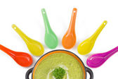 Green cream soup with colorful spoons isolated over white backg — Stock Photo