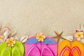 Klapki w piasku z muszli i kwiatów frangipani. srokaty — Zdjęcie stockowe
