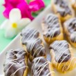 Chocolate éclairs on square white plate — Stockfoto