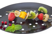 Mini blini (pancake) with cut fruits on skewers — Stock Photo