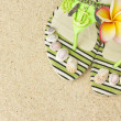 Sandals, seashells, and frangipani on sand — ストック写真