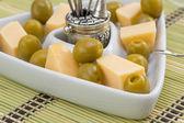 зеленые оливки и сыр закуска в белых треугольных блюдо — Стоковое фото