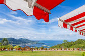 Awning over bright sunny blue sky with bench and sea view — Stock Photo