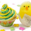 Yellow and green cupcake with toy chick and multicolored decorat - Stock Photo