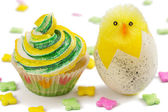 Yellow and green cupcake with toy chick and multicolored decorat — Stock Photo