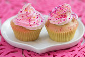 Two cupcake on white heart shaped plate, on pink background — Stock Photo