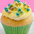 Single cupcake with yellow buttercream and colorful decorations, — Stock Photo