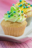 Two cupcakes with yellow and green buttercream and colorful de — Stock Photo