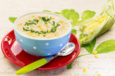 Cream of corn soup in blue bowl — Stock Photo
