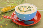 Cream of corn soup in blue bowl with fresh cob of corn on the si — Foto de Stock
