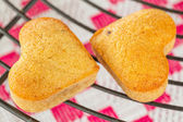 Ywo Homemade heart shaped banana muffins cooling on metal rack — Stock Photo
