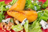 Salad with caramelised pears,walnuts and blue cheese, on red pla — Stock fotografie
