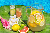 Jug of home made iced lemonade on edge of swimming pool — Stock Photo